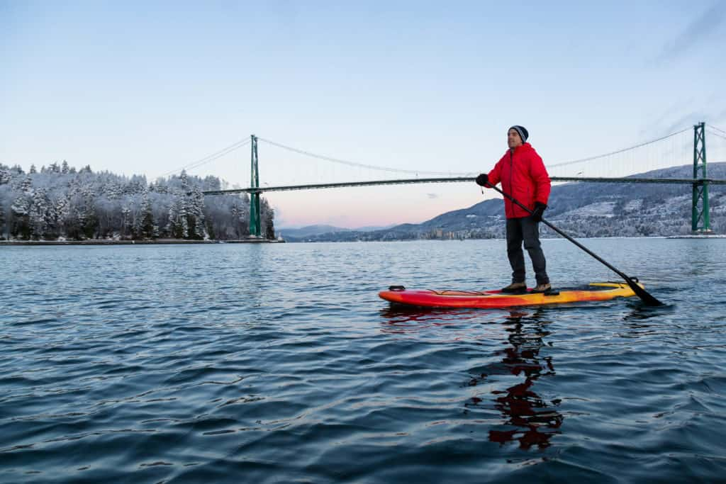 Adventurous man on a Standup Paddle Board is padding near Lions Gate Bridge during a vibrant winter sunrise. Taken in Vancouver, British Columbia, Canada.