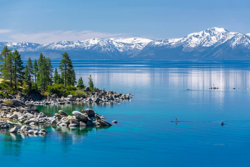 Picture of Lake Tahoe from east shore. There is a snow on the Sierra Nevada Mountains and some white clouds with reflection in turquoise waters of the lake. There is a paddle boarder arriving to the beach. Sand Harbor State Park is visible on the left side of the photograph.