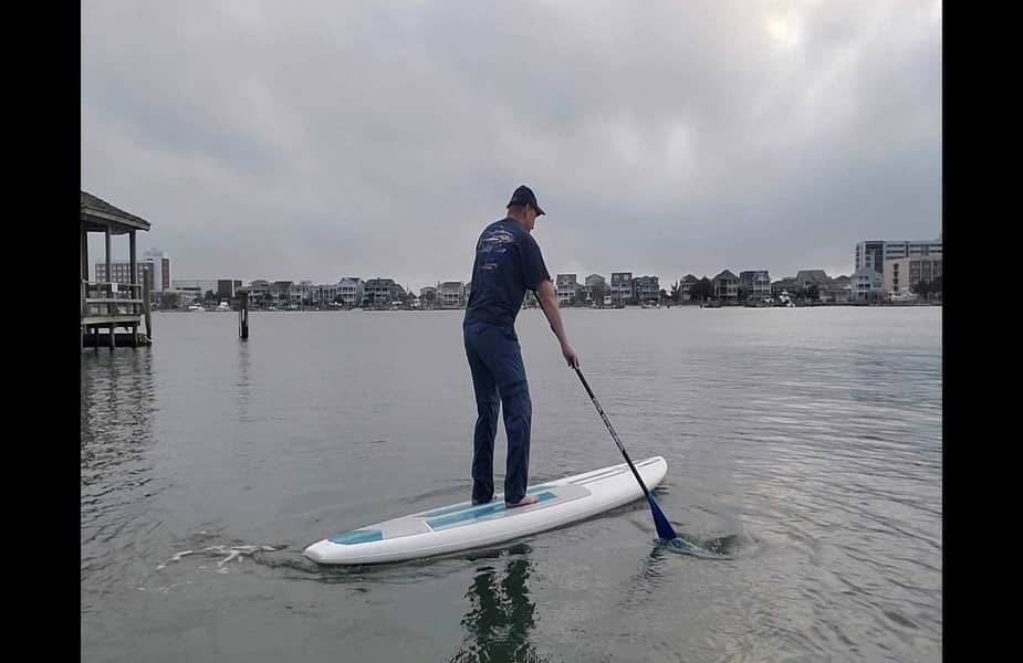 Man Keeping a Stand Up Paddleboard Straight