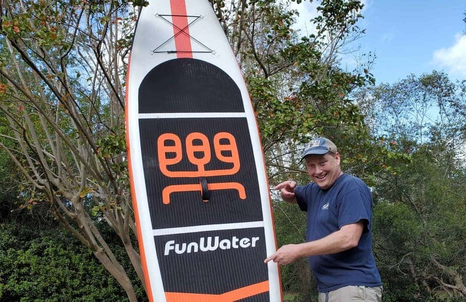 Man Pointing at an Inflatable Stand Up Paddleboard