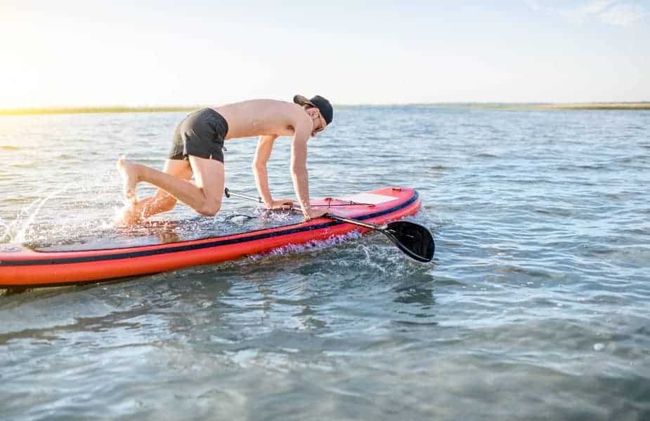 Man on Hands and Knees on a Stand Up Paddleboard