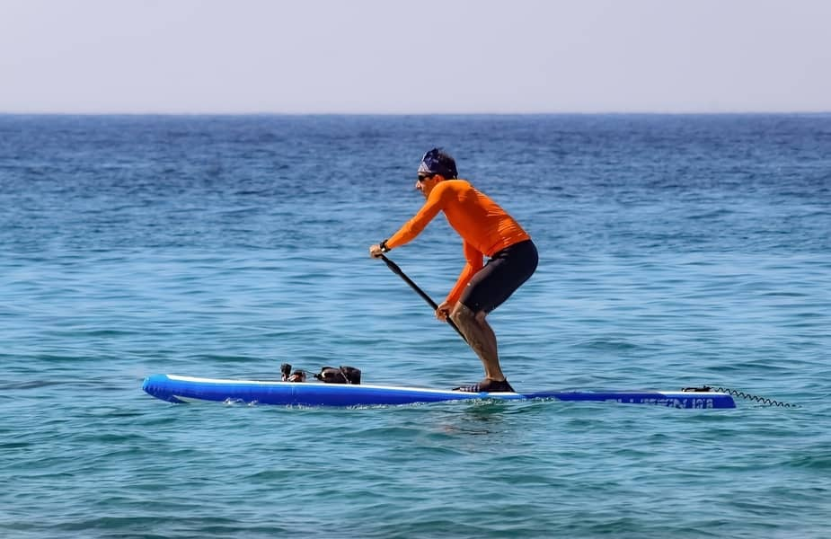 Man Paddleboarding with Shoes On